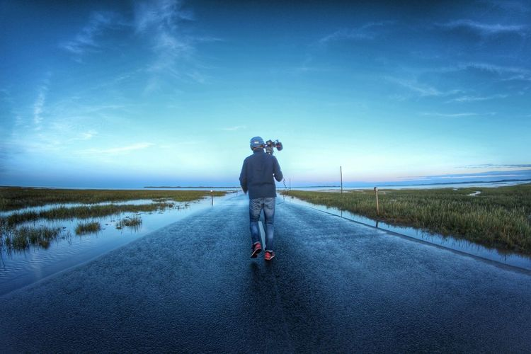 Rear View Of Man Holding Movie Camera While Walking On Road Against Sky