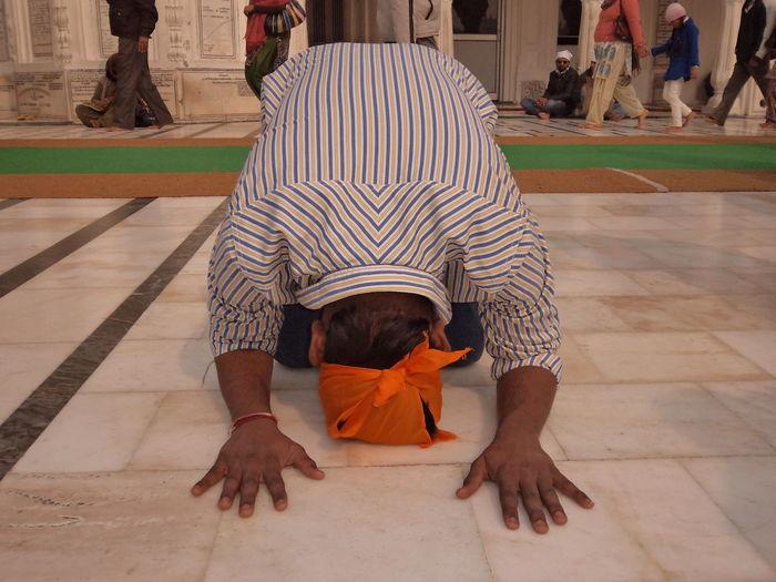 Man kneeling while praying on tiled floor at gurdwara