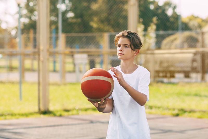 Boy playing with ball in basketball court
