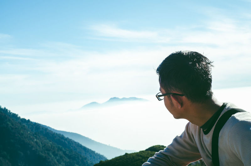 Close-up of young man on mountain against sky