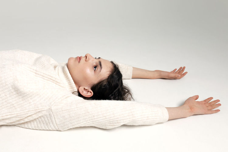 Portrait of young woman lying on white background