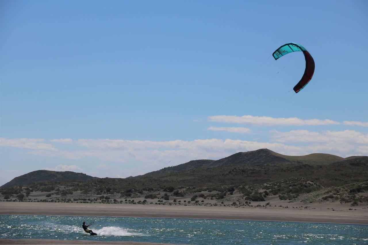 Man Paragliding On Sea Against Sky