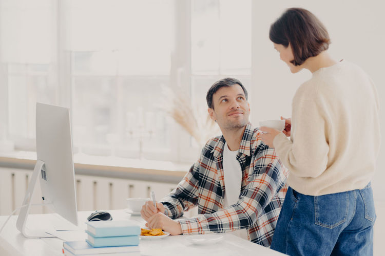 Woman talking with man working at home