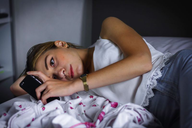Close-up of young woman using laptop on bed at home