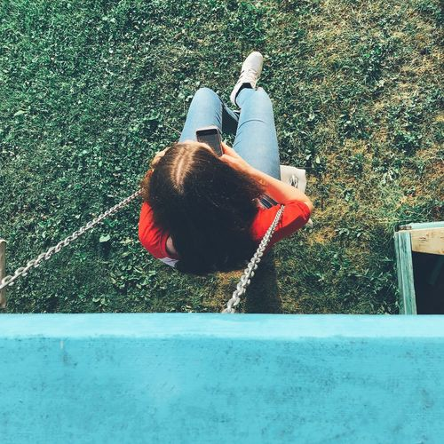 High angle view of woman using smart phone while swinging in park