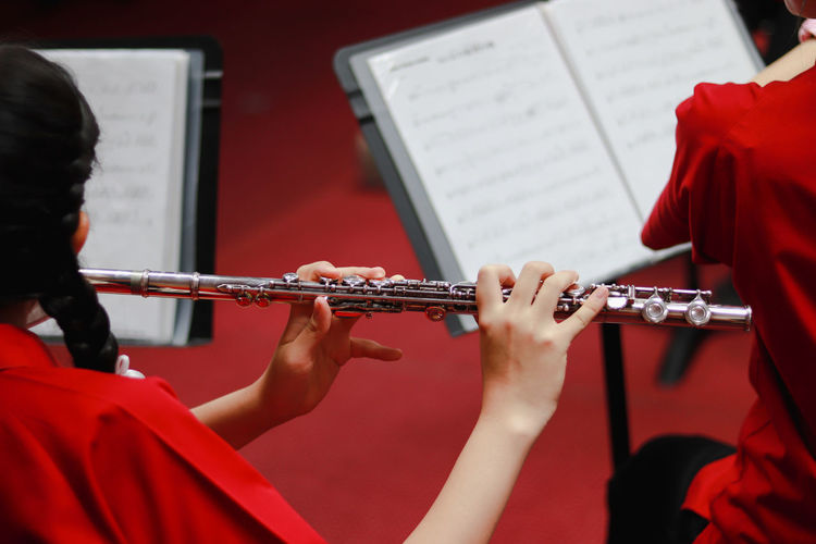 Flute Studen Artist Arts Culture And Entertainment Brass Brass Instrument  Flut Focus On Foreground Hairstyle Holding Music Musical Instrument Musician Paper People Performance Playing Real People Rear View Red Sheet Sheet Music Skill  Trumpet Wind Instrument