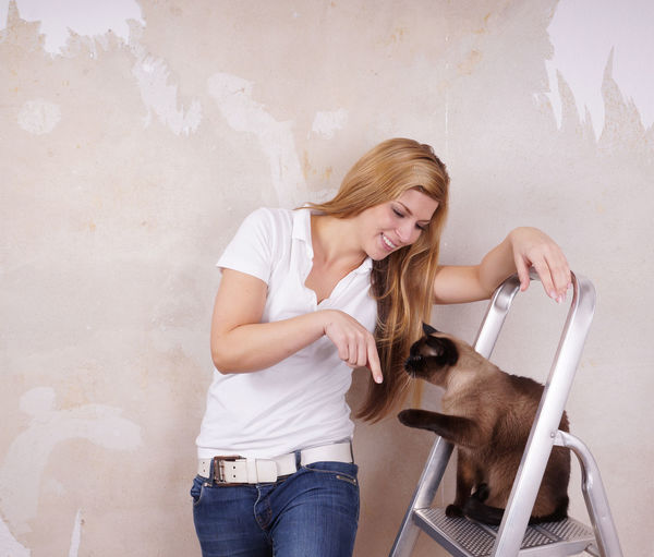 Smiling beautiful woman with siamese cat on ladder against wall