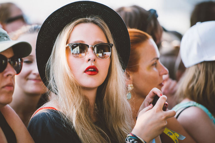 Confidence  Crowd Fans For The Love Of Music Front View Happiness Hat Head And Shoulders Lifestyles Looking At Camera Person Portrait Real People Red Lips Sunglasses Young Adult Young Folks Young Women Women Around The World