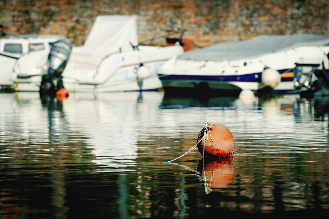 Buoy Floating On Lake Against Boats