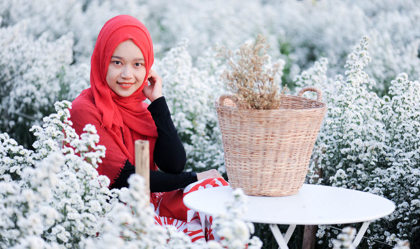 Portrait of smiling woman with red flowers in snow