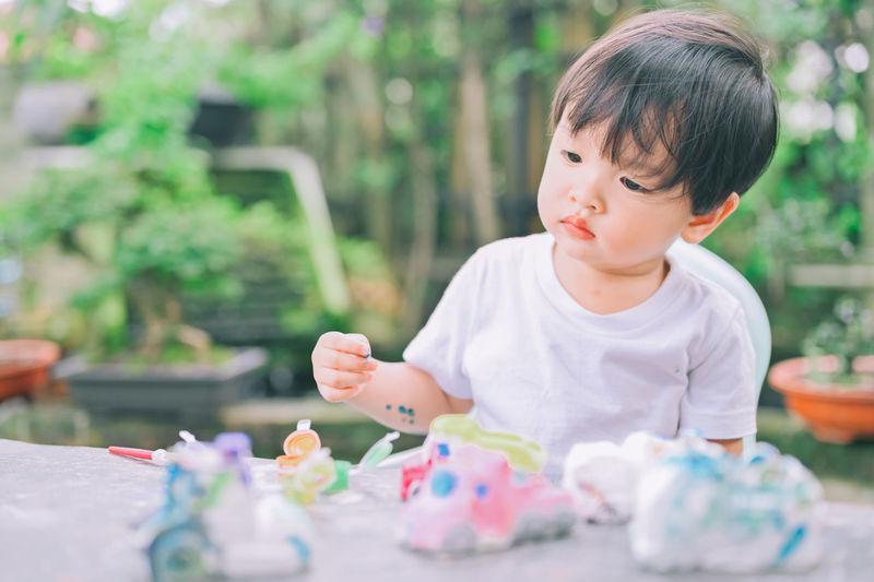 Full length of boy holding ice cream on table