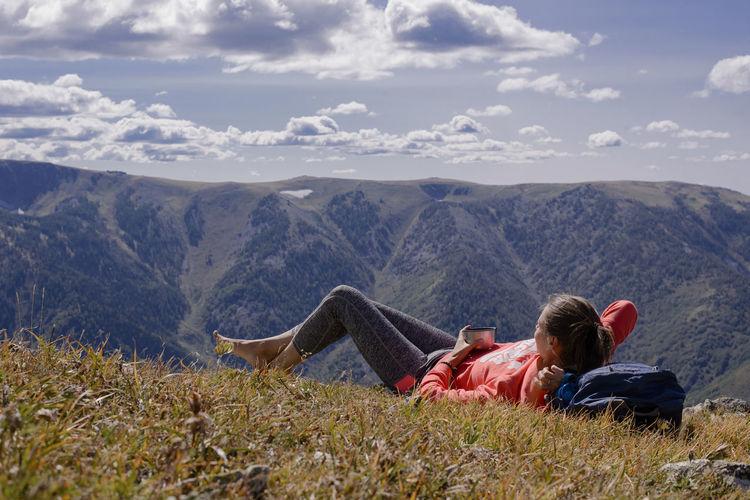 Woman lying on field against mountain