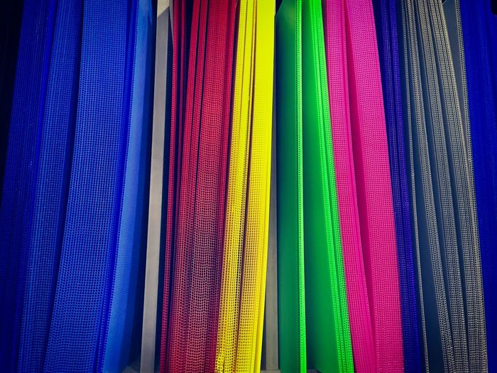Vibrant Corrugated Plastic Sheets on Shelf Plastic Sheet Backgrounds Blue Choice Close-up Corrugated Sheet Day Full Frame In A Row Indoors  Multi Colored No People Spectrum Textile Textured  Variation Vibrant Color