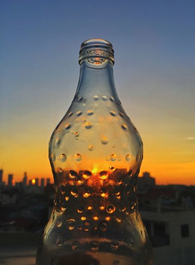 Close-up of glass bottle against sky during sunset