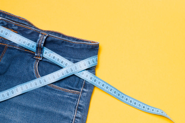 Close-up of jeans with tape measures over colored background