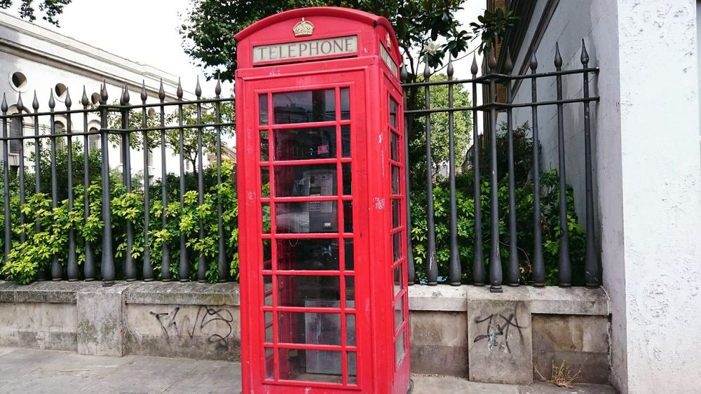 Big red outside Christ Church in Spitalfields Outdoors Capital Cities  Hello World EyeEm Gallery No People Eye4photography  Focus On Foreground Colour Of Life EyeEm Best Shots Famous Place Historical Sights Telephone Telephone Box Communication Red Phone Box Red Colour Tree Nature Connection City Railing British Culture Architecture Phone Booth