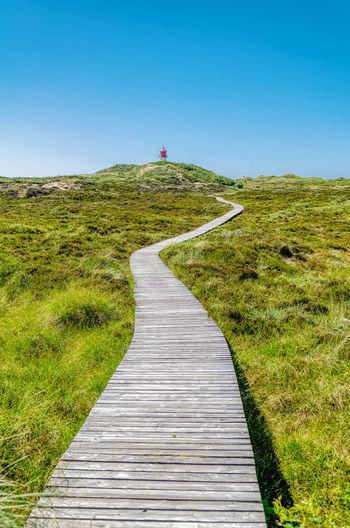 Boardwalk leading towards landscape against clear sky