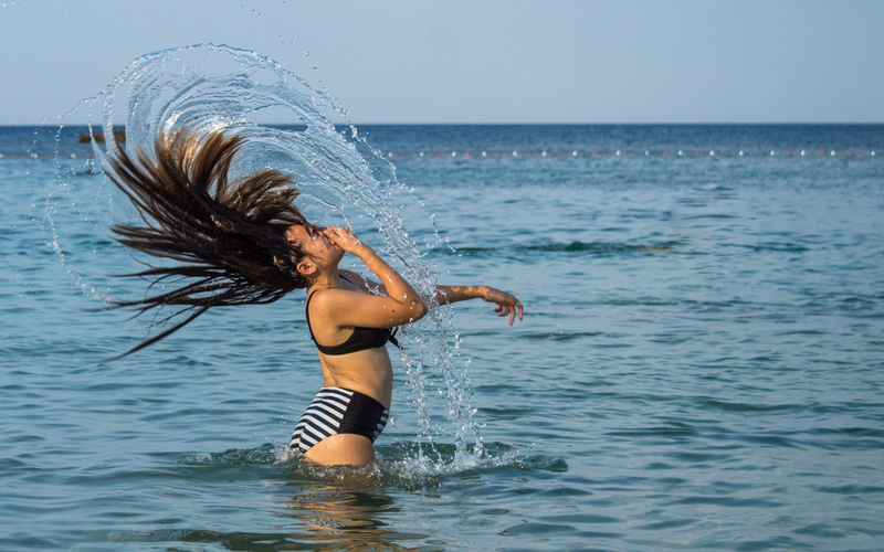 Side view of woman tossing hair while standing in sea against sky