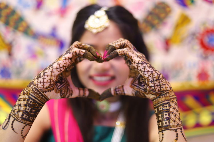 Smiling bride with henna tattoo making heart shape