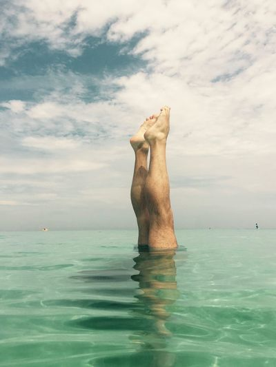Upside down image of man in sea against cloudy sky