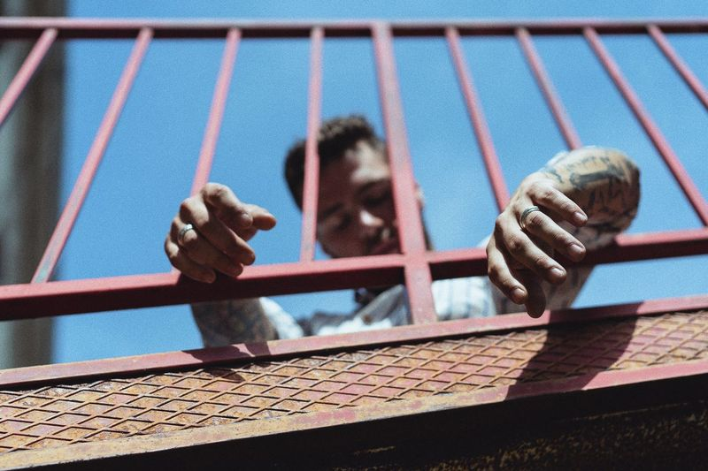 Low Angle View Of Man Seen Through Railing