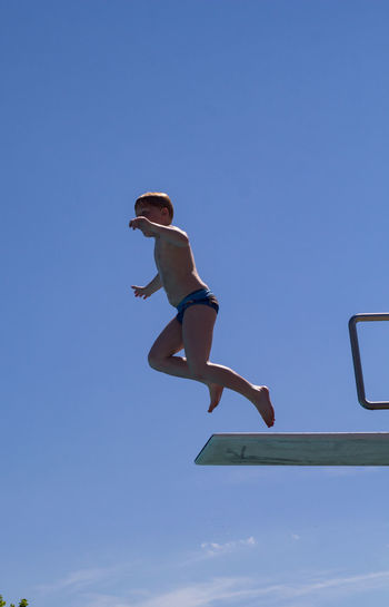 Sport Jumping Full Length Mid-air One Person Motion People Blue Activity Vitality Speed Agility Sky Swimming Jumpboard Jumping In Pool Summer