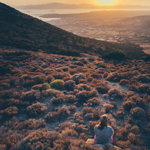 Rear view of woman sitting on mountain during sunset