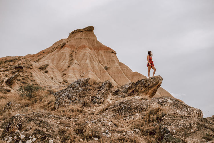 Low angle view of woman on rock against sky