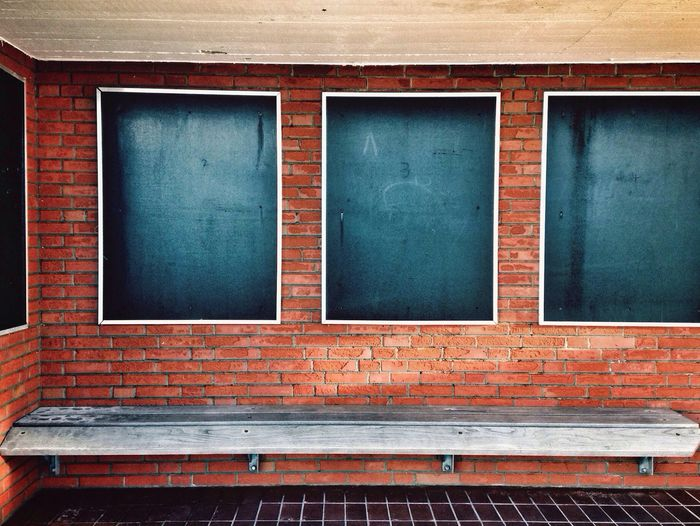 Empty wooden bench against brick wall