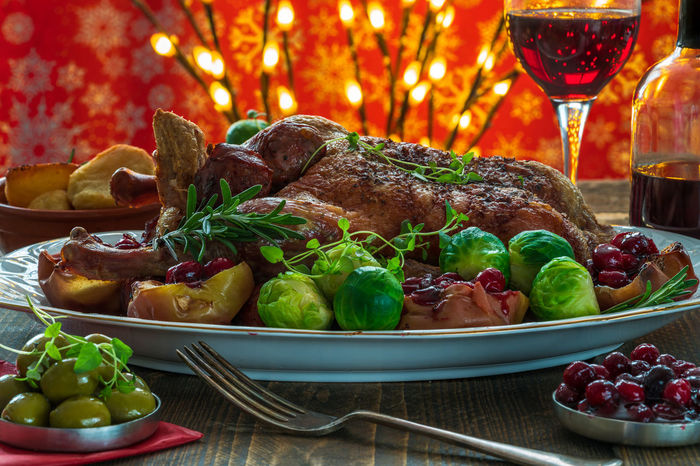 Festive roast duck on wooden table with brussel sprouts, baked potatoes, apples and cranberry sauce on wooden table Christmas Food Dinner Holidays Roast Duck Xmas Baked Brussel Sprouts Close-up Cranberry Sauce  Festive Food Food Food And Drink Freshness Fruit Indoors  Meat No People Plate Ready-to-eat Roast Potatoes Stuffed Apples Table Vegetable Wine Wineglass