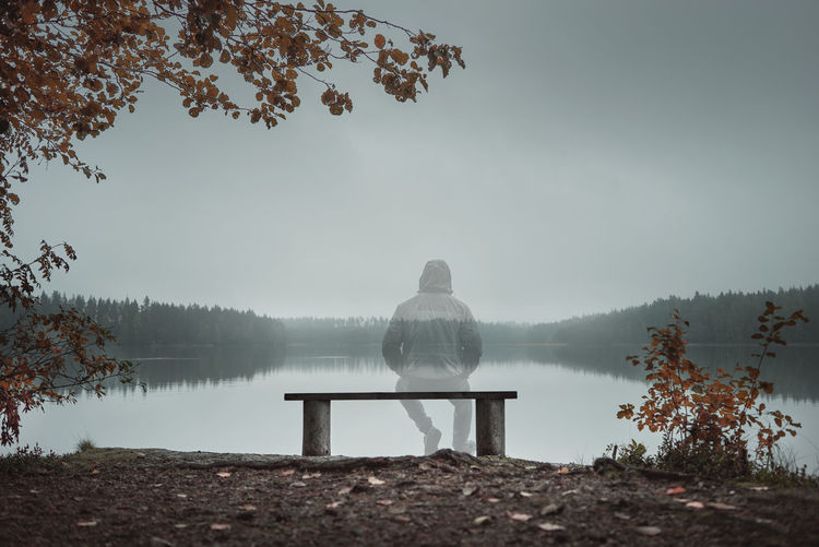 Lonely man sitting on bench at lake against sky