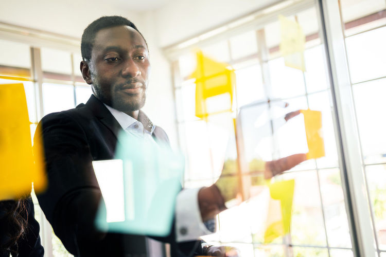 Businessman holding adhesive notes on glass