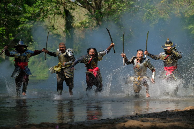 Angry male warriors with weapons running in lake at forest