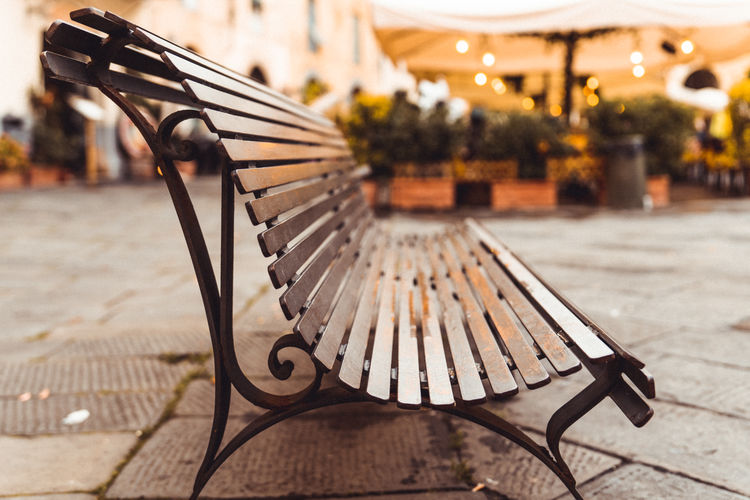 Empty bench on footpath in city