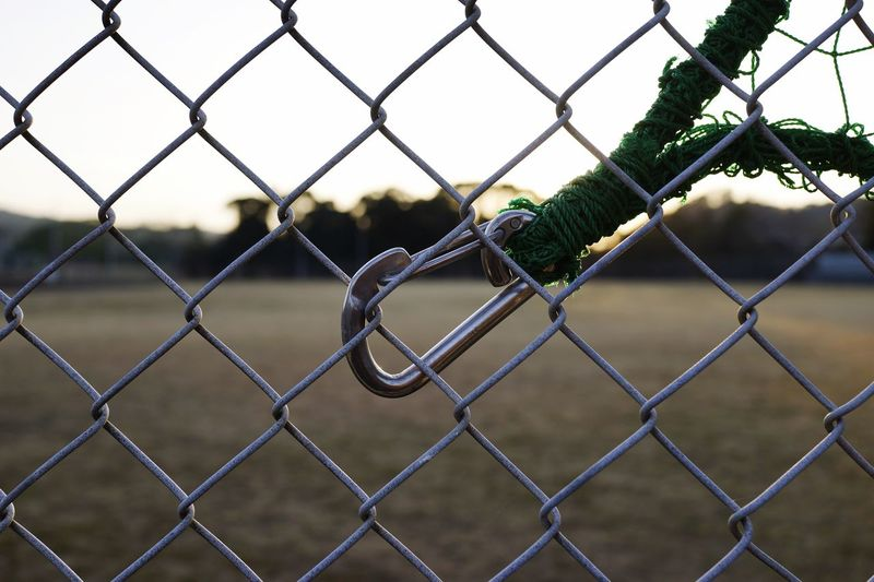 Close-up of carabiner on chainlink fence
