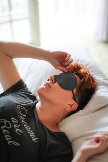 Woman wearing eye mask relaxing on bed at home
