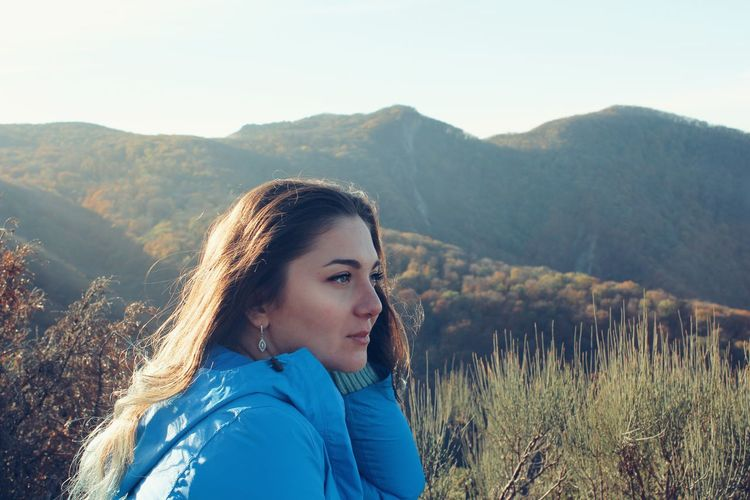 Portrait of beautiful woman against mountains