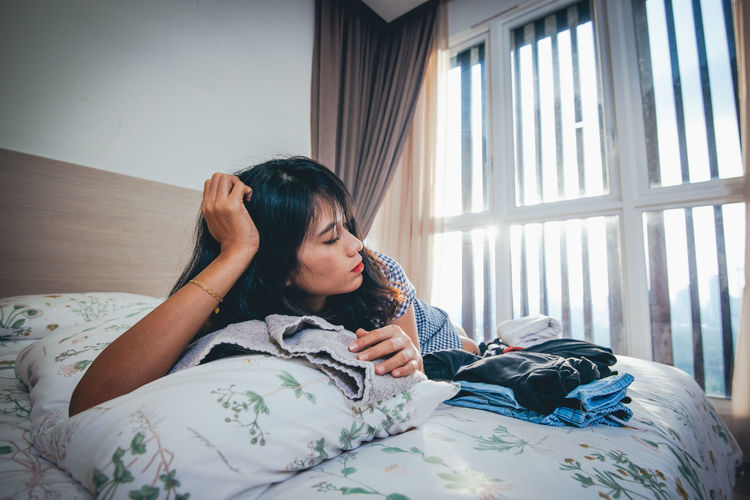 Tired young woman lying on bed at home