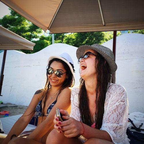 Happy Friends Sitting Below Parasol
