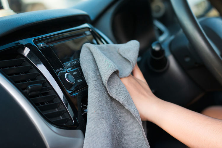 Midsection Of Woman Cleaning Control Panel In Car With Napkin