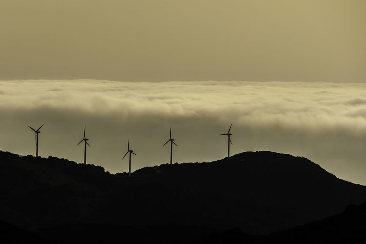 Windmills on silhouette landscape against sky during sunset