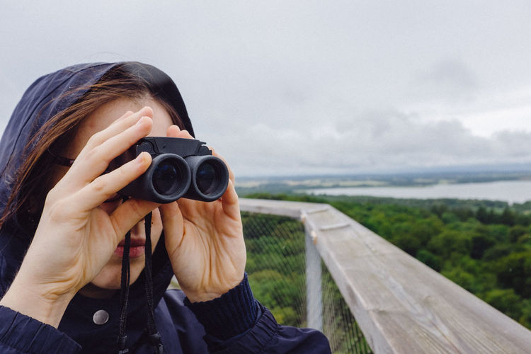 Close-Up Of Woman Looking Through Binoculars At Observation Point