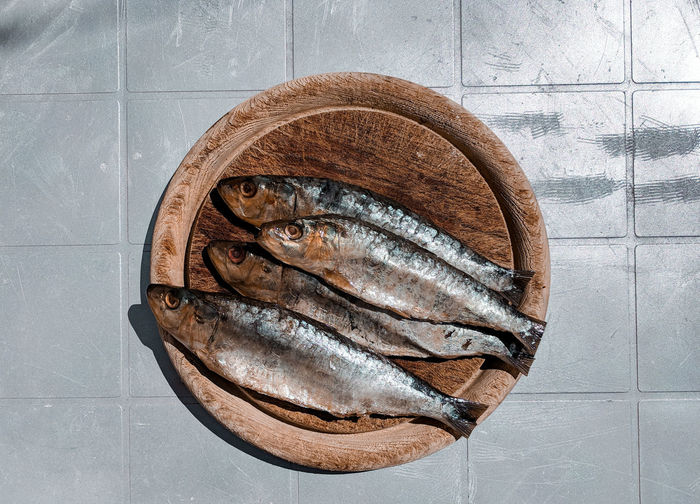 lovely sardines Fish Fishes Sardines Food Cutting Board Table Silver Colored Old Wood Old Plastic Flat Lay Sunlight Sunlit Natural Light Still Life Directly Above Close-up Prepared Food Served Wooden Textured  Rough Rugged Ready-to-eat