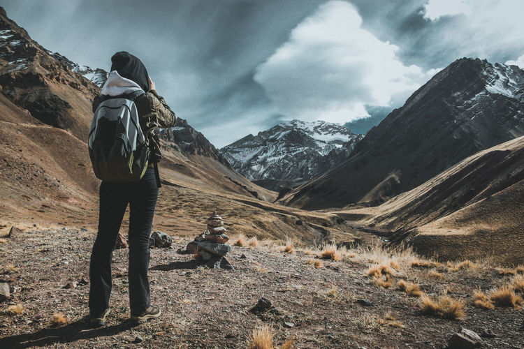 Rear View Of Woman Hiking On Field Against Sky
