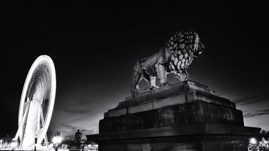 Lion Statue With The Big Wheel Light Trial At Place De La Concorde Against Sky