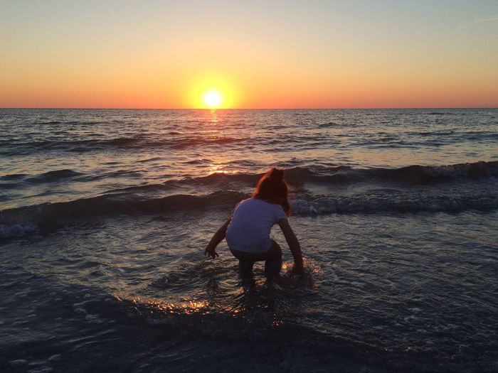 Girl playing with water in sea against sky during sunset