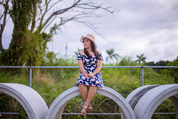 Full length of young woman sitting on concrete tube against plants