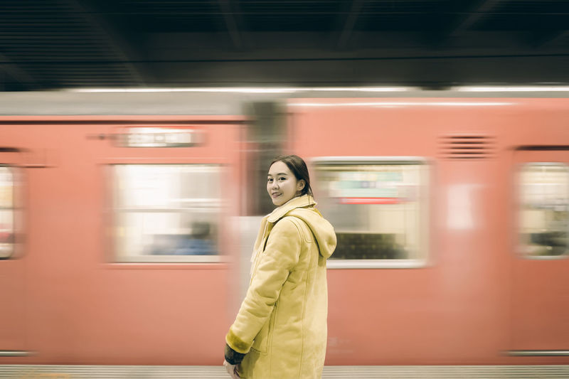 Portrait of woman standing against train moving at railroad station