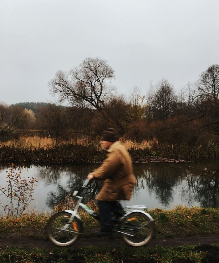 SIDE VIEW OF MAN RIDING BICYCLE BY LAKE