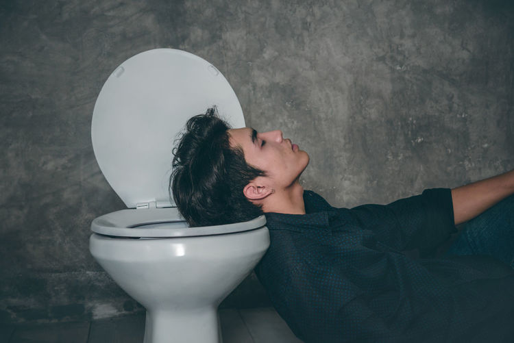 Young man sleeping on toilet bowl in bathroom at home